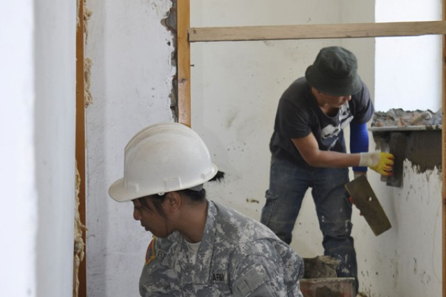 ULAANBAATAR, Mongolia - Pfc. Marvie Punzalan, 797th Engineer Company from Barrigada, Guam, inspects a wall while a Mongolian soldier continues to work Aug. 15 in the district of Songinokhairkhan. Soldiers from both the 797th and the Mongolia Armed Forces are building a public bath house facility as part of a humanitarian and civic assistance project during exercise Khaan Quest.