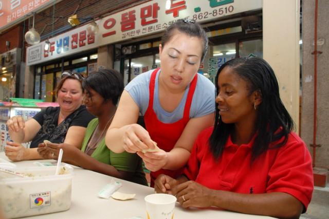 An employee from the Eudum Mandu Restaurant at Jungang Market in Dongducheon helps an Army spouse make traditional Korean mandu from scratch during a city tour.