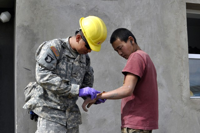 Sgt. Edward Antonio, a medic with the Alaska Army National Guard's 297th Military Police Company from Juneau, Alaska, treats a cut on the arm of Sgt. Galbadrehk Galae, Mongolia Armed Forces. Galae was being treated on the humanitarian and civic assistance project site in the Songinokhairkhan of Ulaanbaatar, Mongolia Aug. 16. Sgt. Antonio is working with the 797th Engineering Company (Vertical) from Barrigada, Guam and the Mongolian Armed Forces during Khaan Quest 2010. Sgt. Antonio is responsible for providing medical support to both U.S. and Mongolian participants.