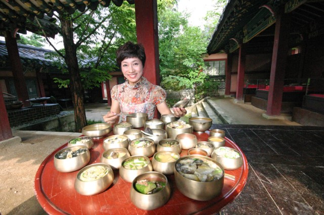 "YANGJU, South Korea - A visitor to the Daejanggeum Theme Park in Yangju sits down in front of replica palace cuisine called ""surasang,"" which consists of 12 side dishes all prepared using different cooking methods."
