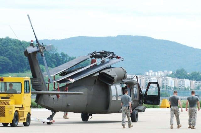 Soldiers from the 2nd (Assault) Battalion, 2nd Aviation Regiment, 2nd Combat Aviation Brigade move a UH-60 Blackhawk from a hangar at Seoul Air Base Aug. 11 following a severe weather exercise conducted in preparation for tropical storm Dianmu. Once the storm passes, Soldiers must take the helicopters out of the hangar and unfold the blades. The aviation unit conducts weather training several times a year to ensure readiness for the Korean monsoon season.