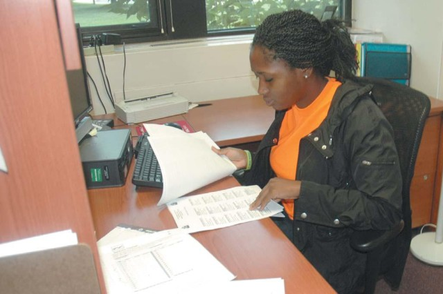 Janaye Oliver, 16, a HIRED! apprentice working at the Kirk U.S. Army Health Clinic's Referral Management Office, reviews some paperwork.