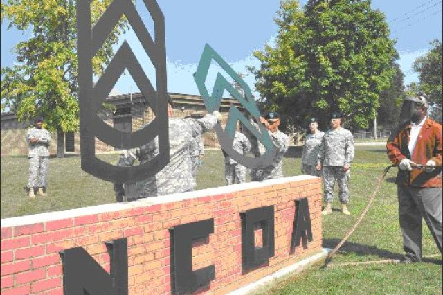 Retired Command Sgt. Maj. Sammy Brinson, right, in welding gear, looks on as Sgt. 1st Class Michael Moore, center and Staff Sgt. Brian Sharp, left, remove the E-6 chevron from the Noncommissioned Officer Academy wall August 11. Brinson is a former commandant of the Academy.
