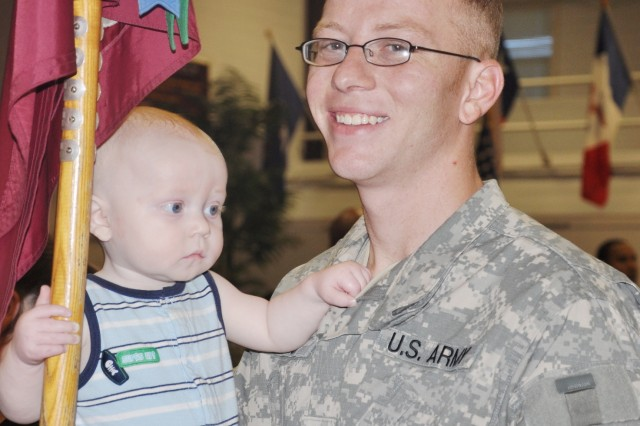 Zack Lane, 9 months old, holds on tightly to his father Spc. Tyler Lane and the 591st guidon after the deployment ceremony Aug. 11.