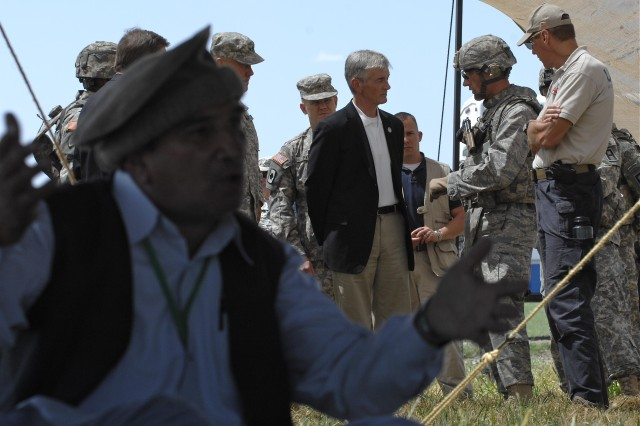 Secretary of the Army John McHugh, center, visits with Provincial Reconstruction Team Zabul Commander Lt. Col. Andy Veres as the team participates in a training scenario to prepare them for their upcoming deployment at Camp Atterbury Joint Maneuver Training Center, Ind., Aug. 18.