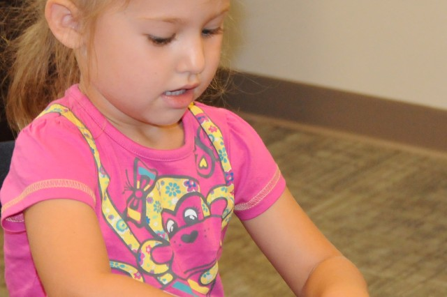 "Hannah Hokanson, 3, places a set of eyes on her ""Curious George"" door hanger at the Fort Rucker Center Library Aug. 10."