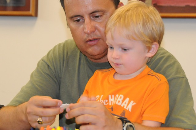 "Mike Shannon, 1st Bn., 11th Avn. Regt executive officer, and his son, Samuel, work together on a craft at the Fort Rucker Center Library's ""Curious George"" celebration Aug. 10. Mike said spending time with his son at the event was a great way to spend his day off."