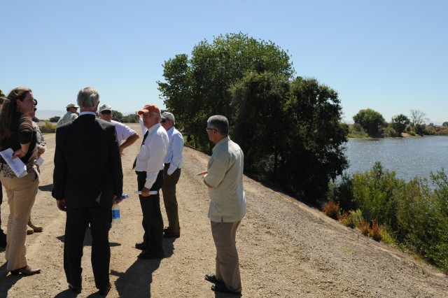 """Attendees of a meeting on San Joaquin County flood protection initiatives stand on top of a levee near Stockton, Calif., Aug. 17. The U.S. Army Corps of Engineers South Pacific Division and Sacramento District participated in the meeting, hosted by the San Joaquin County Flood Control and Water Conservation District in order to brief Brig. Gen. Scott F. """"Rock"""" Donahue, commander of the South Pacific Division. The event included a tour of local flood protection projects in and around Stockton and other San Joaquin County cities."""