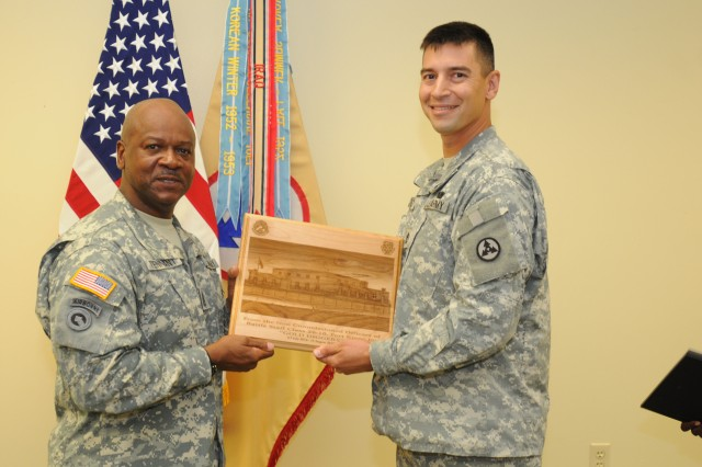 Sgt. 1st Class Aaron Loos, a maintenance management noncommissioned officer with the 3d Sustainment Command (Expeditionary) and Rochester N.Y. native, presents Command Sgt. Maj. Willie C. Tennant, 3d ESC senior enlisted leader, with a plaque for his participation in the Battle Staff Noncommissioned Officer Course graduation Friday, August 13 at Skidgel Hall. Tennant was the guest speaker for the event, which included the graduation of eleven Soldiers from the 3d ESC. (U.S. Army photo by Sgt. Michael Behlin)