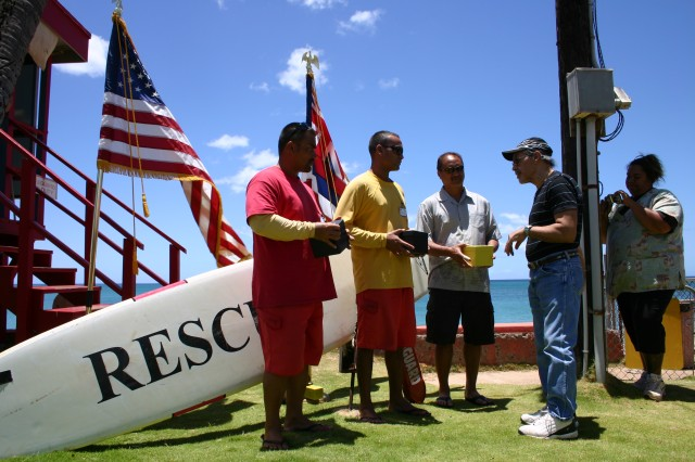 WAIANAE, Hawaii - In an appreciation ceremony at the Pililaau Army Recreation Center, Gilbert Rodriguez (far right) presents his rescuers, Hizson Lin-Kee (left) and Russell Purdy (center), both lifeguards, and Theo Auwau (right), a surfer on the scene, with Invicta watches, as a thank-you gift for saving his life, after he nearly drowned while walking in the water, recently.