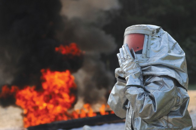 A PWD instructor adjusts her mask as the fire burns in the background during fire suppression training held Aug. 10.  The trainining is part of the petroleum supply specialist course taught at the Quartermaster School.