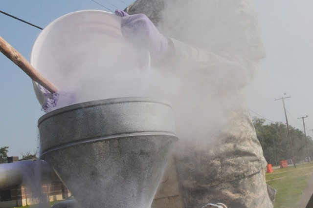 Pvt. Adrian Council, Uniform Company, 262nd QM Battalion, 23rd QM Brigade, mixes Purple K Powder, a chemical fire suppression agent, during training at Fort Lee Aug. 10.  About 75 AIT Soldiers underwent training to suppress fuel fires at the Quartermaster School's Petroleum and Water Department fire pit training area.