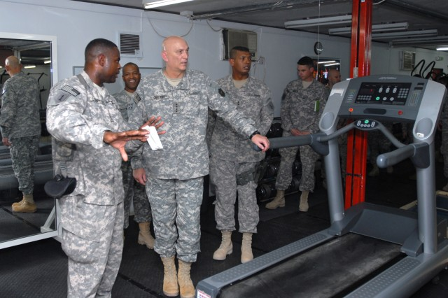 Sgt. Maj. Teddy R. Compton, the 1st Infantry Division's personnel sergeant major from Burlington, N.C., and coordinator for the physical pillar and cross-fit gym at the resiliency campus on Contingency Operating Base Basra, explains some of the resources available to Soldiers at the campus to Gen. Ray Odierno, United States Forces-Iraq commander Aug. 18 as Maj. Gen. Vincent K. Brooks, United States Division-South and 1st Infantry Div. commander, looks on. The room is set up so that Soldiers can move through cardio and weight-based training quickly and without long lines.
