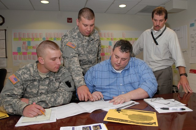 Bill Stevens (seated right) works with Spc. Jerome Solt (standing), a Firefinder radar repair technician, and Pfc. John Eisenhauer, a Firefinder radar operator, to map out the repair process for the AN/TPQ-37 Firefinder as Chris Simko observes.  The Soldiers are with the Pennsylvania Army National Guard's 55th Heavy Combat Brigade, 1/109th Field Artillery.  The event was held at Tobyhanna Army Depot, Pa.