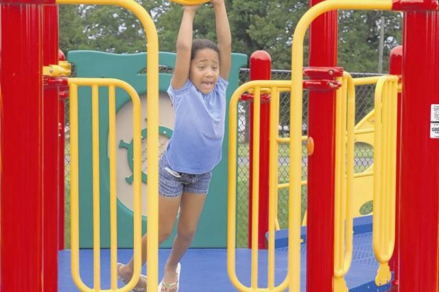 Emma Funderburke, 7, tries to climb across the hoops on the Boundless Playground Saturday.