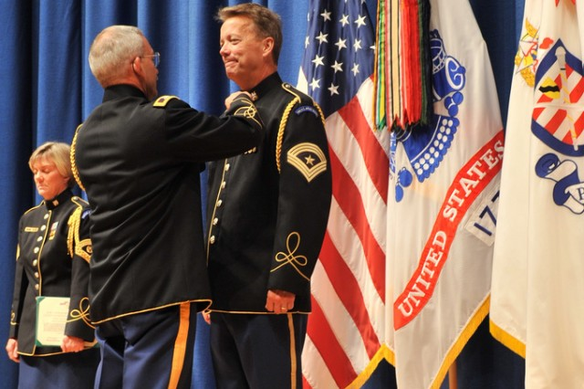 """Col. Thomas Rotondi, Jr., Commander of """"Pershing's Own,"""" pins the Legion of Merit Medal onto Sgt. Maj. Woodrow English's uniform.   Sgt. Maj. Woodrow """"Woody"""" English, the Army Band's Senior Trumpet Soloist and Special Bugler, retired after 34 years of service at Ft. Myer, Thursday, August 19."""