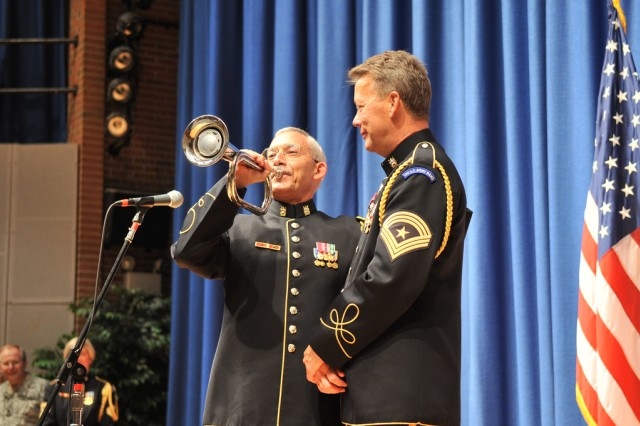 "Col. Thomas Rotondi, Jr., Commander of ""Pershing's Own,"" demonstrates the ceremonial bugle presented to Sgt. Maj. Woodrow English. The bugle, now used all over the country at military installations where trumpet players are in short supply, features a recording of Sgt. Maj. English performing ""Taps"" at the 1999 Memorial Day Wreath Laying Ceremony at Arlington National Cemetery."