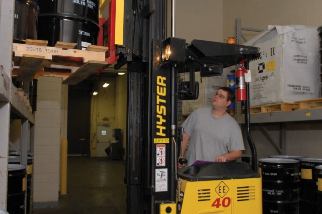 Matt Argust, an environmental protection specialist, places hazardous waste on a storage rack until it is shipped off the installation.