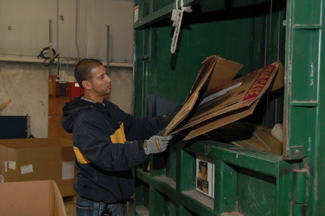 Jason Sabater, a recycling employee, loads scrap cardboard into a baler for recycling.