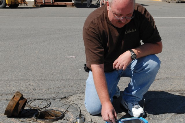 Tom Wildoner, an environmental protection specialist, tests a drinking water leak detection sensor.