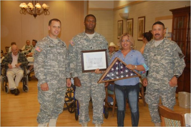 Col. Scott McKean, commander of the 4th Brigade Combat Team, 1st Armored Division, Sgt. 1st Class Alexander Petty, noncommissioned officer-in-charge for the Highlanders legal affairs section, and Command Sgt. Maj. Phillip Pandy, senior noncommissioned officer of the Highlander Brigade present a certificate and a flag that was flown over the Highlanders headquarters during their recent deployment to Iraq, to Josie Ramirez, the activities coordinator for the Ambrosio Guillen Texas State Veterans Home. The Highlanders wanted to express their appreciation to the veterans and reaffirm a commitment to an ever-growing relationship with them. (U.S. Army photo by Spc. Bradley J. Clark, 4th Brigade Combat Team, 1st Armored Division public affairs)