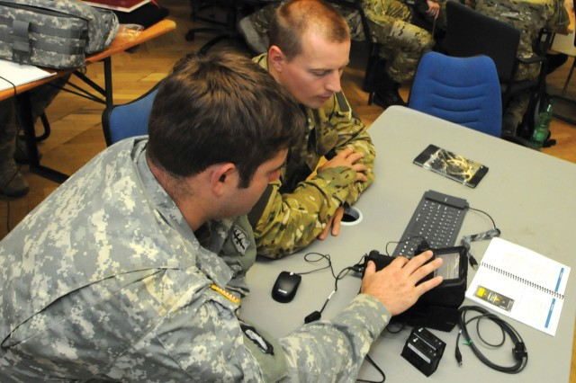 A U.S. military intelligence NCO assigned to 1-10th SFG (Airborne), left, demonstrates how to use the Secure Electronic Enrollment Kit to an intel officer assigned to the Poland Special Operations Command Aug. 11 on Panzer Kaserne.