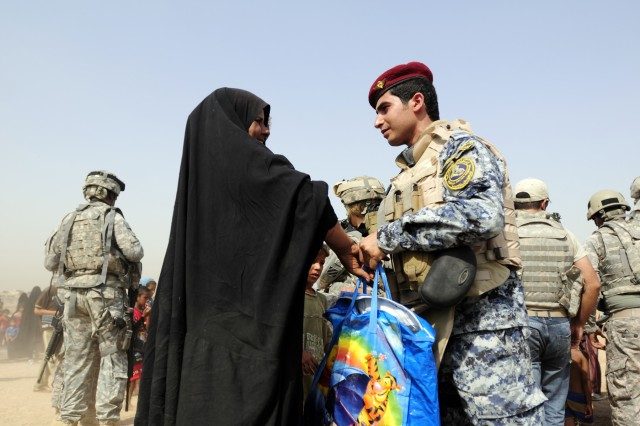 BAGHDAD - An Iraqi Federal Policeman (right) hands out a bag of food and supplies to an Iraqi woman during a humanitarian aid drop outside Contingency Operating Station Falcon. The bags contained enough food to feed a family for seven days. (U.S. Army photo by Spc. Jared Eastman, 1st AAB, 3rd Inf. Div., USD-C)