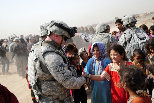 BAGHDAD - Col. Roger Cloutier (left), commander of 1st Advise and Assist Brigade, 3rd Infantry Division, United States Division - Center, shakes hands with an Iraqi girl Aug. 10 during a humanitarian aid drop outside Contingency Operating Station Falcon. (U.S. Army photo by Spc. Jared Eastman, 1st AAB, 3rd Inf. Div., USD-C)