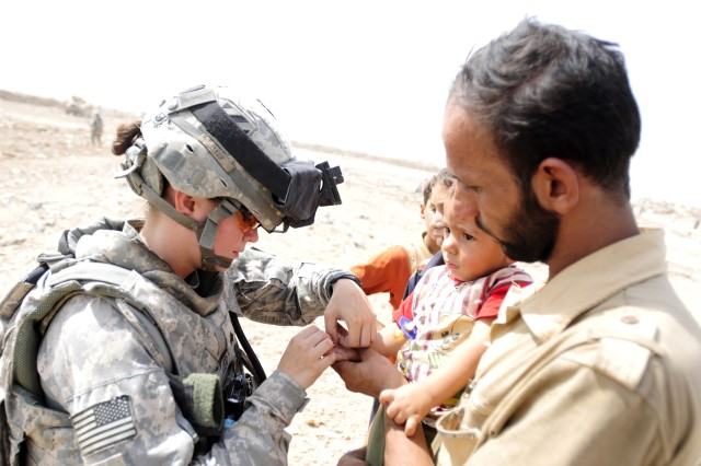 BAGHDAD - Sgt. Kate Lyker (left), a medic with 1st Advise and Assist Brigade, 3rd Infantry Division, United States Division - Center, bandages up a child's finger Aug. 10 during a humanitarian aid drop outside Contingency Operating Station Falcon. (U.S. Army photo by Spc. Jared Eastman, 1st AAB, 3rd Inf. Div., USD-C)