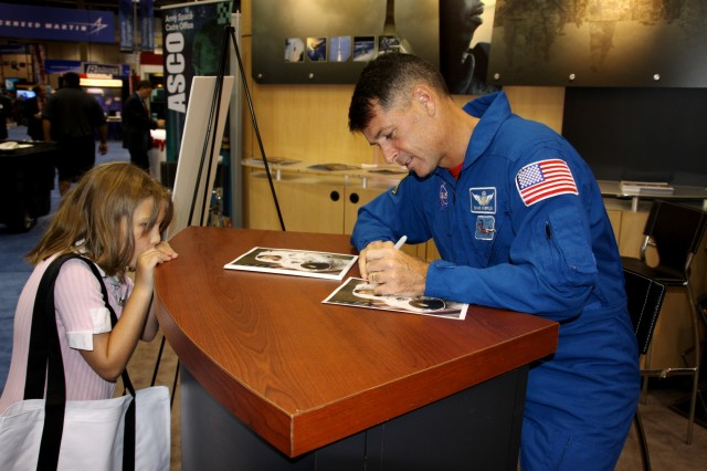 Army Astronaut Lt. Col. Shane Kimbrough autographs photographs for visitors at the U.S. Army Space and Missile Defense Command/Army Forces Strategic Command exhibit during the 13th Annual SMD Conference at the Von Braun Center Aug. 16-19 in Huntsville, Ala. Kimbrough completed his first space flight on STS-126 in 2008, logging a total of 15 days, 20 hours, 29 minutes and 37 seconds in space, and 12 hours and 52 minutes of EVA in 2 space walks.