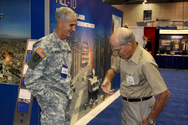 Lt. Gen. Kevin T. Campbell, U.S. Army Space and Missile Defense Command/Army Forces Strategic Command commanding general, coins World War II Veteran Earl Anderson after speaking with him during the 13th Annual Space and Missile Defense Conference at the Von Braun Center in Huntsville, Ala., Aug. 16-19.