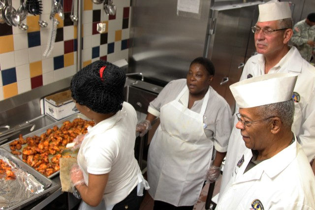FORT LEE, Va. - Jim Riddle (bottom right) and Ronald Coneybeer (top right), large garrison food service evaluators for the Philip A. Connelly Food Service Awards Program, receive a tour of the Ordnance Campus dining facility during the Connelly Evaluator's Workshop, August 23-25. The purpose of the program is to improve professionalism in food service through recognition for excellence.  Each year, from October to December, evaluators travel the globe to obtain first-hand knowledge of how Army food service personnel perform their jobs. Winners and runners-up are recognized in the categories of large and small garrisons, along with Active Army, Reserve and National Guard field kitchens.