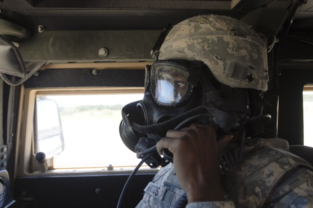 FORT HOOD, Texas-Sgt. Darren Woods, a recon security detachment member with 215th Brigade Support Battalion, 3rd Brigade Combat Team, 1st Cavalry Division, executes crew fire commands, Aug. 20, while wearing a gas mask as part of the brigade's gunnery exercise. The battalion is the first of its kind in the division to participate in the exercise.