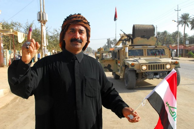 An Iraqi man near a Karbala polling site displays his marked finger - a sign of having voted - during the Iraqi national elections March 7 while Iraqi Security Forces stand guard in their humvee. The elections were the second national vote since the ousting of Saddam Hussein and the first secured completely by Iraqi Security Forces.