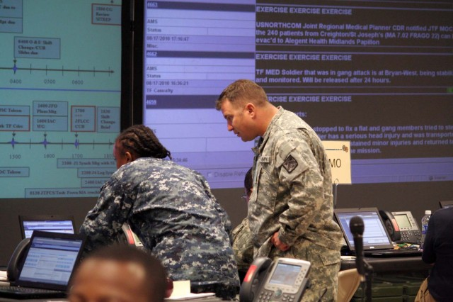 Sgt. 1st Class Richard Ross, a movement and maneuver observer/trainer, advises a sailor on operations at the Battle Command Training Center during the Command Post Exercise for Joint Task Force Civil Support in Ft. Leavenworth, Kansas on August 18.