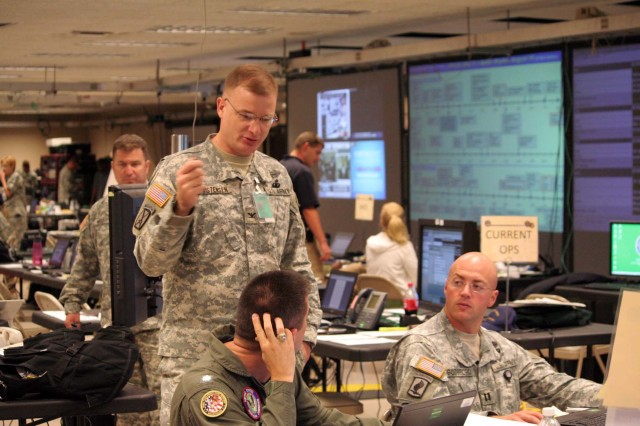 Col. Thomas Christensen, Chief of OPSGRP Alpha discusses current operations on the Joint Operations Center (JOC) floor with JOC personnel at the Battle Command Training Center during the command post exercise for Joint Task Force Civil Support in Ft. Leavenworth, Kansas on August 18.