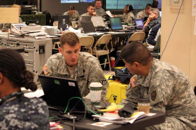 Lt. Col. Jon Clausen, chief intelligence observer/trainer, OPSGRP Alpha discusses intelligence operations with the J2, Lt. Col. Alex Espinoza, on the Joint Operations Center floor at the Battle Command Training Center during the command post exercise for Joint Task Force Civil Support in Ft. Leavenworth, Kansas on August 18.