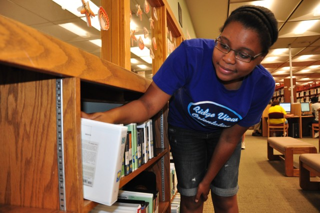 Lavesha Parker, 16, chooses among the compact disc audiobook collection at Thomas Lee Hall Library. Parker likes to listen to her favorite books on CD while driving to and from school. Audiobooks are available in both CD and Playaway format at the library. Like regular books, audiobooks are free to check out.