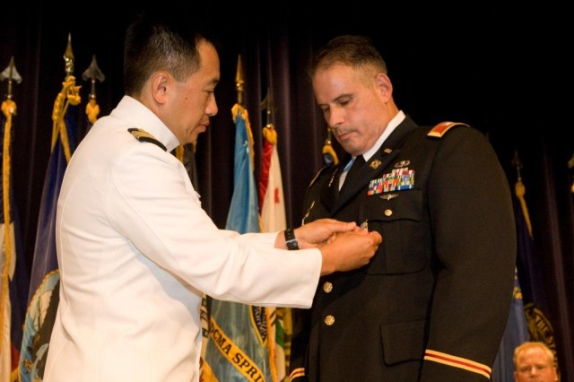 Retiring commander of the Defense Contract Management Agency Springfield, Col. Jack A. Pellicci Jr., receives a medal from Capt. Sydney J. Kim, Eastern Regional Commander for DCMA, at a change of command and retirement ceremony at Picatinny Arsenal, Aug. 4, 2010.