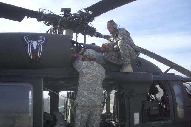 "Chief Warrant Officer Ed Griffie, from Amite, La., and Chief Warrant Officer Greg Alford, from Houston, Texas, both with  Company A, ""SPIDERS"" (4th Battalion, 3rd Aviation Regiment), 1st Battalion, 3rd Aviation Regiment, Task Force Viper, prepare to conduct a high speed shaft vibration check on a Black Hawk engine following 120 hour maintenance, recently, at Forward Operating Base Salerno, Afghanistan."