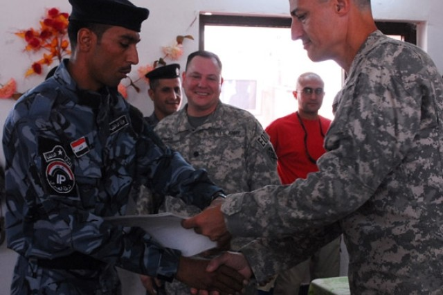 Brigadier General Kenneth Tovo (right), deputy commanding general-west for United States Division - Center, presents an Anbar Iraqi Police Officer with a certificate of completion during a Counter Explosive Team course graduation ceremony at the Ramadi Training Center, Aug. 21.