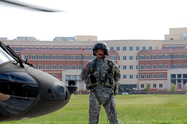 "With the U.S. Army Forces Command and U.S. Army Reserve Command Combined Headquarters Construction Project in the distance, Spec. J.W. Stover, A Company, 3rd Battalion, 82nd Combat Aviation Brigade, crew chief for UH60 Black Hawk ""Mustang Zero-Niner-Three"", awaits passenger arrival on the Main Post Polo Field, Aug. 18, 2010, at Fort Bragg, N.C. Stover, from Parris Island, S.C., wears the 82nd Airborne Division's renowned ""AA"" (All-American) patch on his left and right sleeves. The patch on his left sleeve means he is currently assigned to the 82nd Airborne Division; the patch on the right denotes he has served in combat as a member of the 82nd."