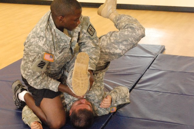 Staff Sgt. Vernon Maybin overturns his combatives partner during a task at the 2010 AIT Platoon Sergeant of the Year Competition. Photo by Carroll Kim
