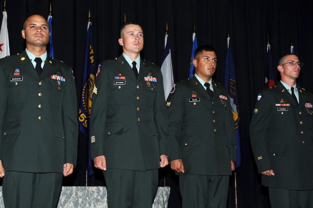 Warrior Leader Course award winners stand to be recognized at their graduation ceremony. From left are Spc. Hector J. Burgosadams, Distinguished Honor Graduate; Sgt. Justin S. Mottoshiski, John D. Magrath Leadership Award recipient; Spc. Juan S. Salais, Commandant's Inspection winner; and Spc. Patrick L. Fraser, Iron Soldier.