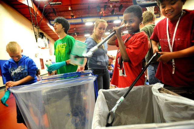 Austin Beach, left, Tristan Resendez, Laqunitt Whitsett and Joshua Co brave their way through a trash audit at the Teen Zone earlier this month as Miriam Easley, JBLM sustainability outreach coordinator, looks on. The teens were learning about the benefits of waste reduction.