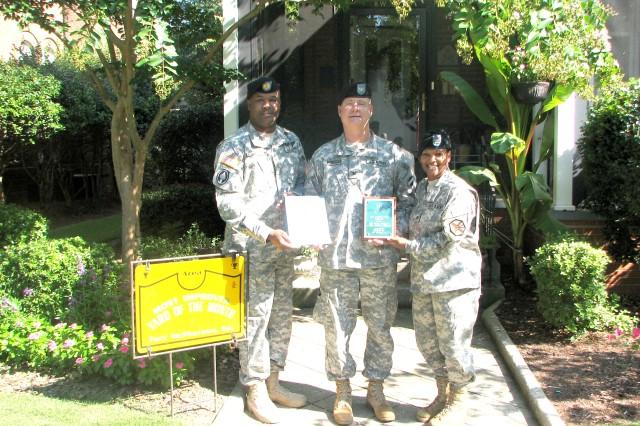 U.S. Army Garrison (USAG) command sergeant major, Command Sgt. Maj. Karl Roberts (left), and USAG commander, Col. Deborah B. Grays, present Col. Steve Horosko, deputy surgeon, U.S. Army Forces Command (FORSCOM), a plaque for most improved yard.