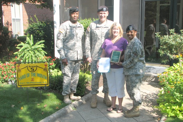 U.S. Army Garrison (USAG) command sergeant major, Command Sgt. Maj. Karl Roberts (left), and USAG commander, Col. Deborah B. Grays, right, congratulate Col. Jessie Farrington, assistant G-3, operations and aviation, FORSCOM, and his wife, Sandra, for the work they did to beautify their home on Staff Row. The couple planted multiple flowers and strung lights in their tree to brighten their home.