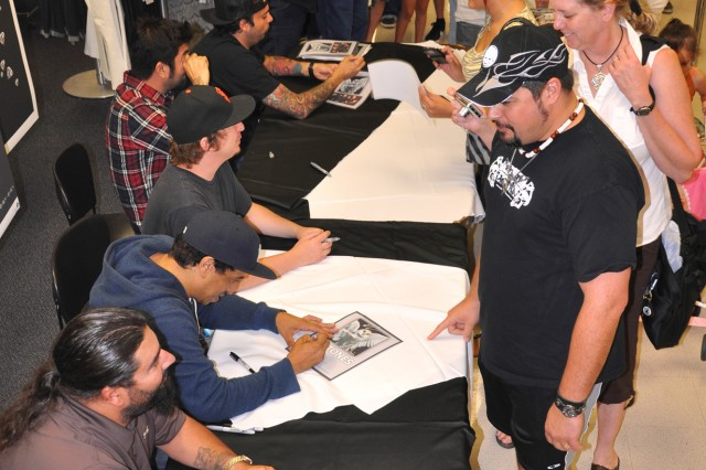 Steve Sinatra (in hat) and his wife, Karen, (right) get their chance for pictures and autographs with the Deftones (seated from left, guitarist Stephen Carpenter, bassist Sergio Vega, drummer Abe Cunningham,  vocalist/guitarist Chino Moreno and keyboardist/turntablist Frank Delgado). Sinatra is a Army Safety Program Manager at Fort Sam Houston and is also front man for the southern metal band Destruction Evolution.