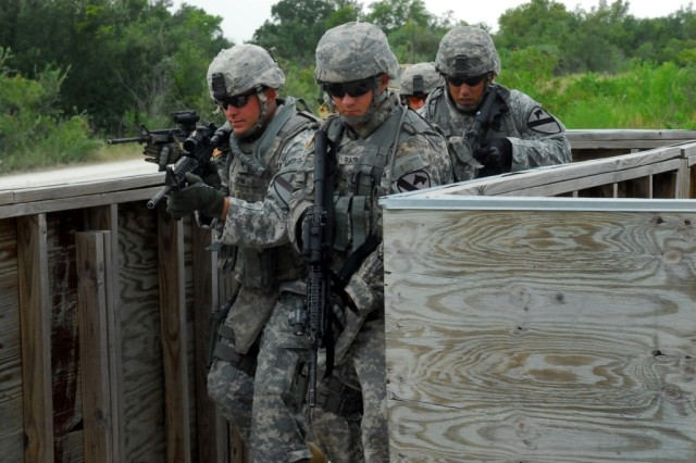 "FORT HOOD, Texas-Military policemen from 2nd Special Troops Battalion, 2nd Brigade Combat Team, 1st Cavalry Division, simulate entering and clearing a building during the Special Reaction Team phase one training at Fort Hood's ""shoot"