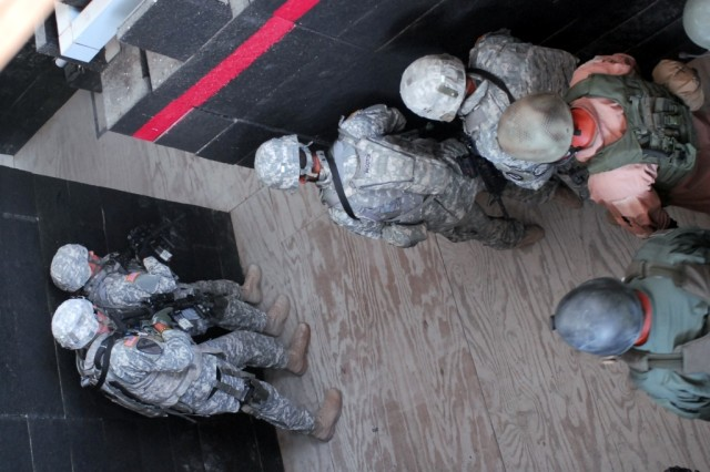 "FORT HOOD, Texas- Military policemen from 2nd Special Troops Battalion, 2nd Brigade Combat Team, 1st Cavalry Division, practice stacking against the walls before clearing rooms during the Special Reaction Team phase one training at the Fort Hood ""shoot house"", Aug. 25."